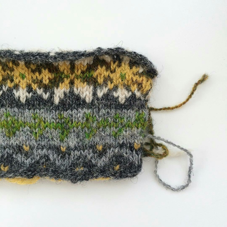 Swatch for my #vestvemberkal Fair Isle vest. I need to work on the colors in the light gray/green stripe, as they're not contrasting enough, but I LOVE that green. I may switch to green background with a white design. #knitting #knit #fairislefriday #fairisleknitting #wool #wovember2015 #projectsweaterchest